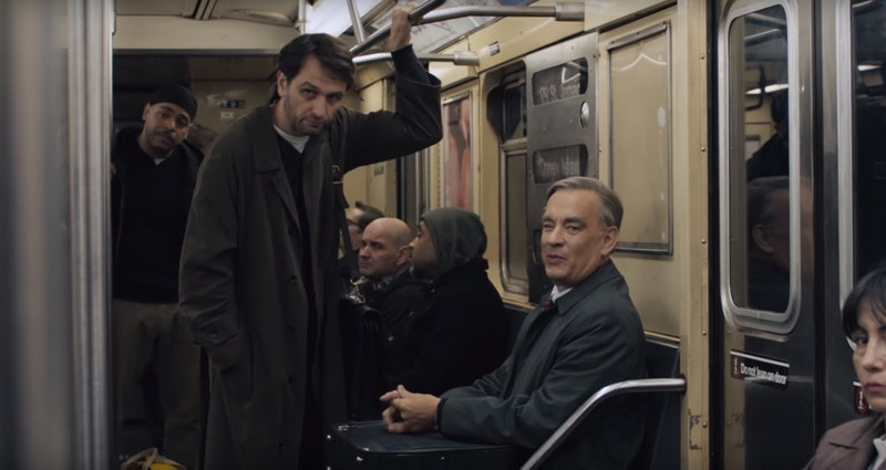 A dark-haired man in a long coat stands above an older man wearing a grey jacket and tie seated in a subway car.