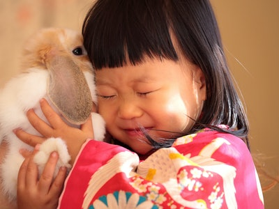 Little girl cuddles a rabbit