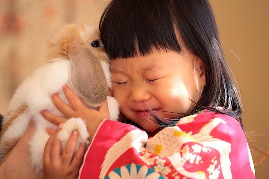 Little girl cuddles a rabbit