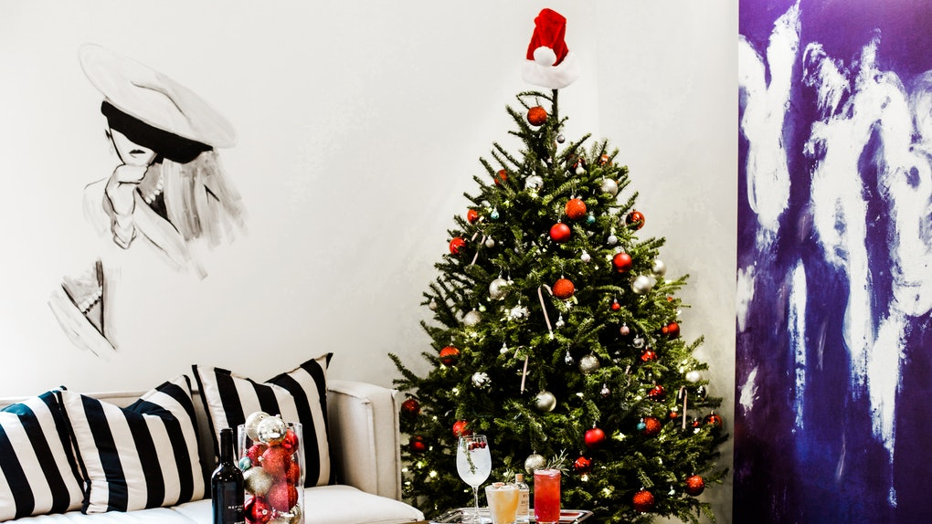 """The interior of a hotel room features a decorated Christmas tree next to a white couch with striped pillows, and a coffee table with a bottle of wine and tray of cocktails at Refinery Hotel's """"Winter Spectacular Stay Package."""""""