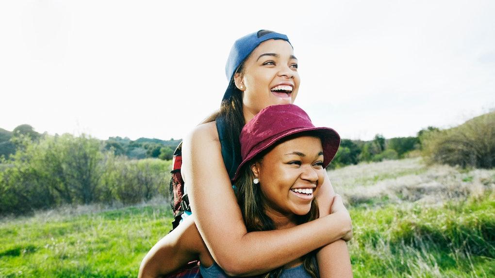 Protective older sister giving younger sister piggyback ride