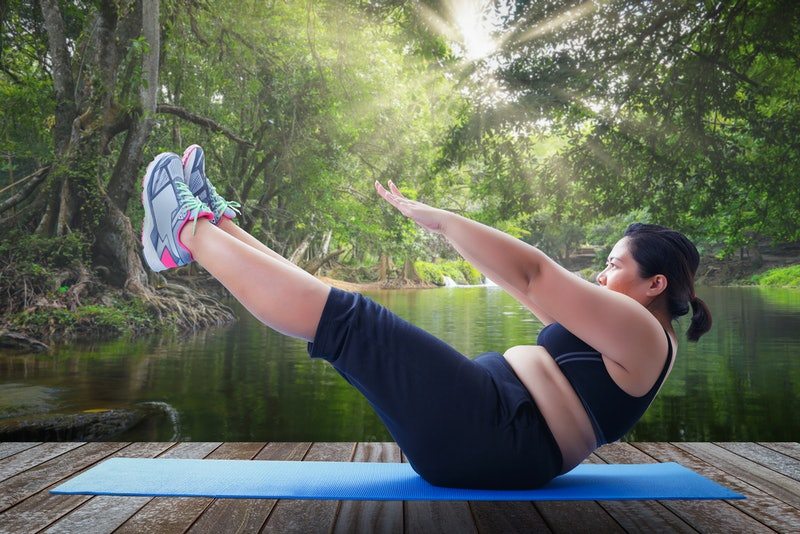 A person holds a yoga pose on a blue mat overlooking a lake. Working out consistently doesn't have to be expensive.
