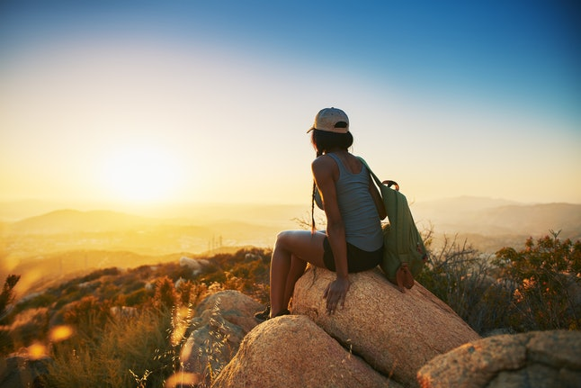 A person in a snapback and tank top with a green backpack sits on a rock while looking out over the sunset. Going on a hike can be an excellent way to work out for free.
