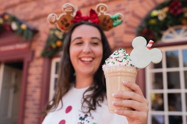 A woman holds a holiday milkshake at Mickey's Very Merry Christmas Party.
