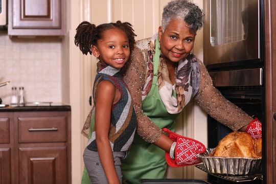 Mom puts turkey in oven for Thanksgiving while little girl helps
