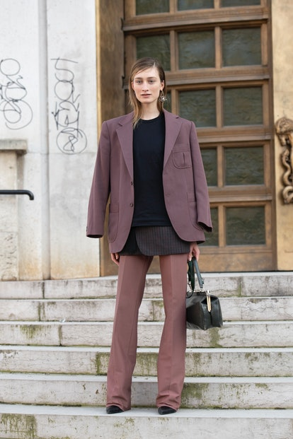 Street style photo of model Felize Kolibius wearing a layered look with a maroon blazer, black sweater, and mauve pants at Paris Fashion Week Fall 2019.