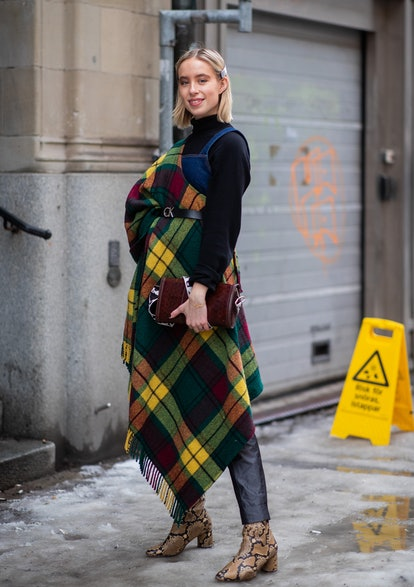 Street style photo of woman wearing a black turtleneck and denim overalls with an oversized plaid scarf layered and belted, plus snakeskin ankle boots at Stockholm Fashion Week.