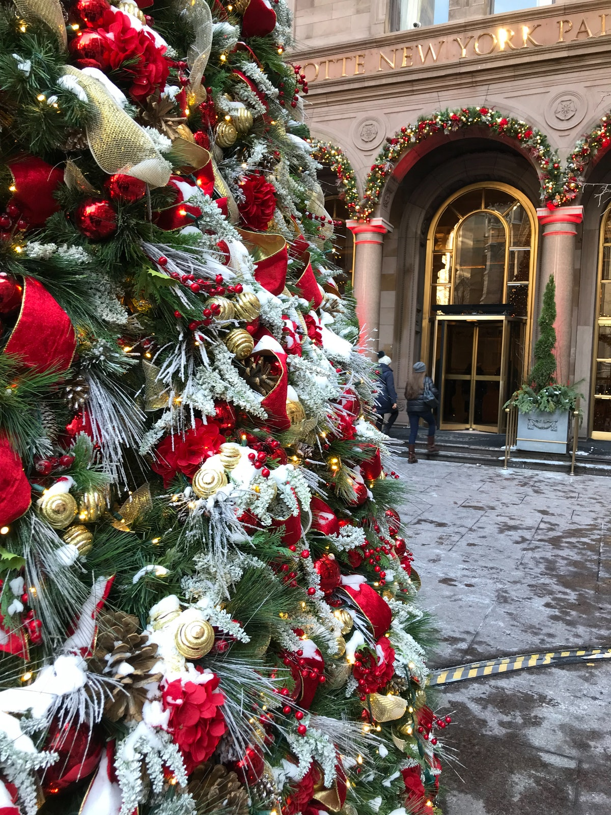 A beautifully-decorated Christmas tree with pinecones, gold accents, string lights, and red flowers is in front of Lotte New York Palace in New York City.