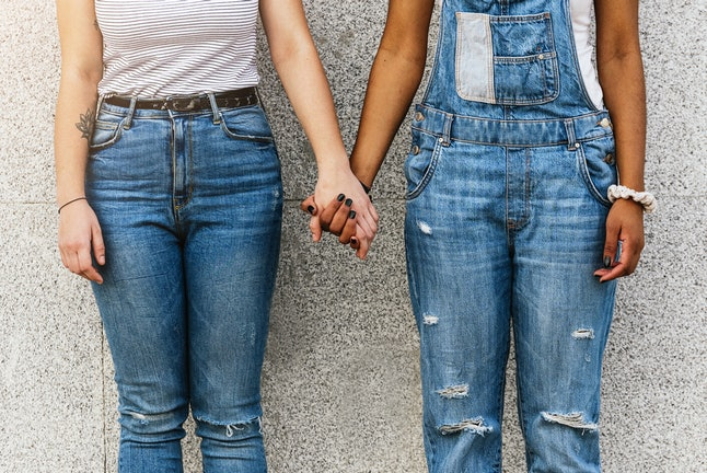 Two people wearing ripped jeans hold hands while standing in front of a concrete wall. When someone in a relationship has a history of trauma, memory issues can make it difficult to commuicate.