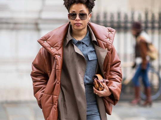 Street style photo of influencer at fashion week dressed in a layered winter outfit featuring Nanushka brown faux leather puffer jacket over a trench coat and a gray wool shirt.