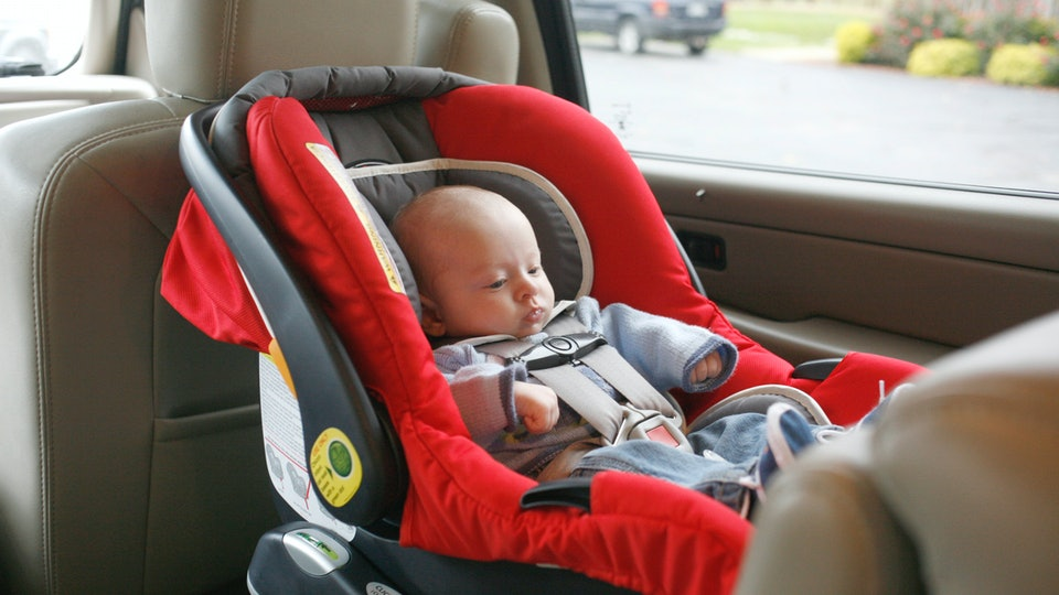 a baby in a light sweater buckled into a car seat