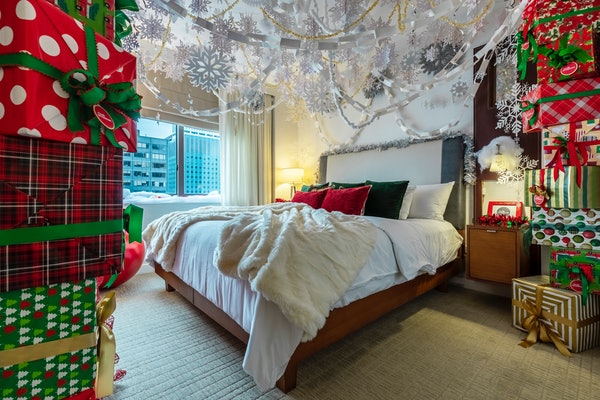The 'Elf'-themed suite at Club Wyndham Midtown 45 features a wall of wrapped presents, television, comfy bed, and view of the city.