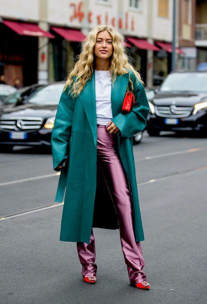 Street style photo of Emili Sindlev wearing a dark teal coat and pink pants at Milan Fashion Week Sp...