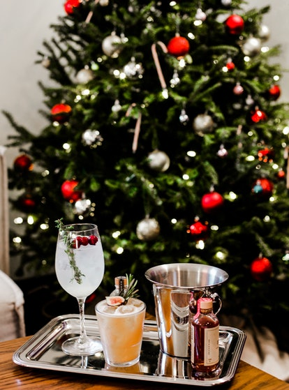 A silver platter of seasonal cocktails sits on a wooden coffee table with a Christmas tree in the ba...