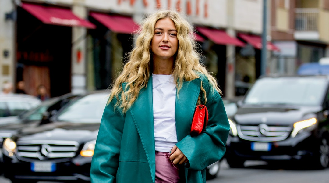 Street style photo of influencer Emili Sindlev wearing a teal leather coat and metallic pink pants at Milan Fashion Week Spring 2020.