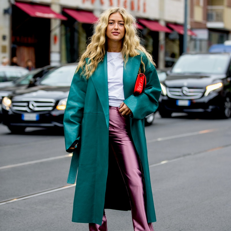 Street style photo of influencer Emili Sindlev wearing a teal leather coat and metallic pink pants a...
