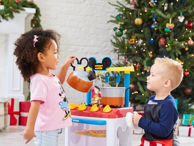 A girl and boy playing with a mickey mouse kitchen from disney