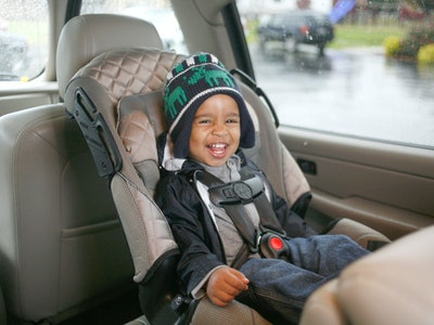 a little boy in a car seat laughing