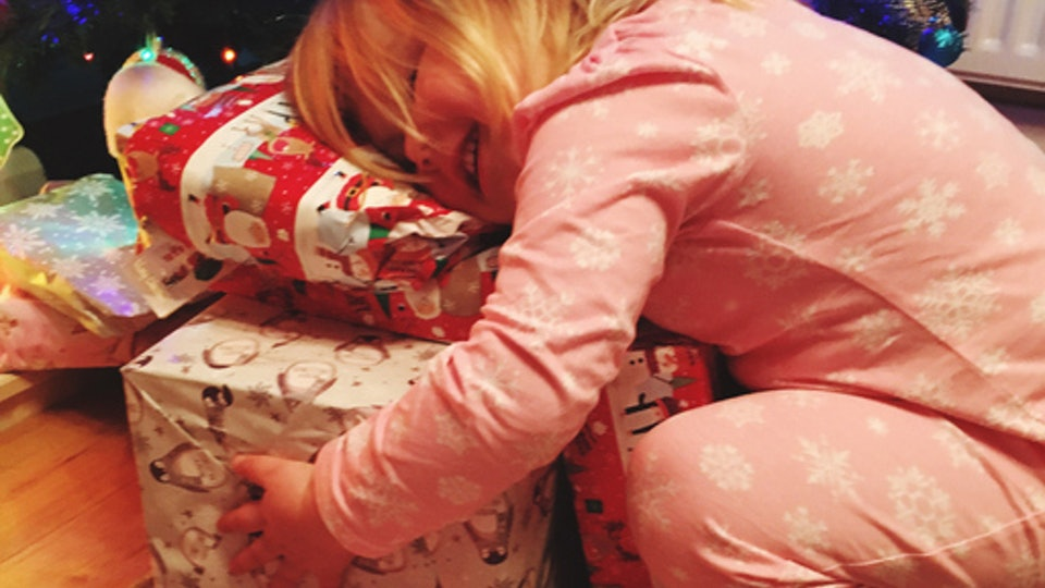 best holiday gifts for toddlers; toddler hugging a stack of wrapped holiday presents