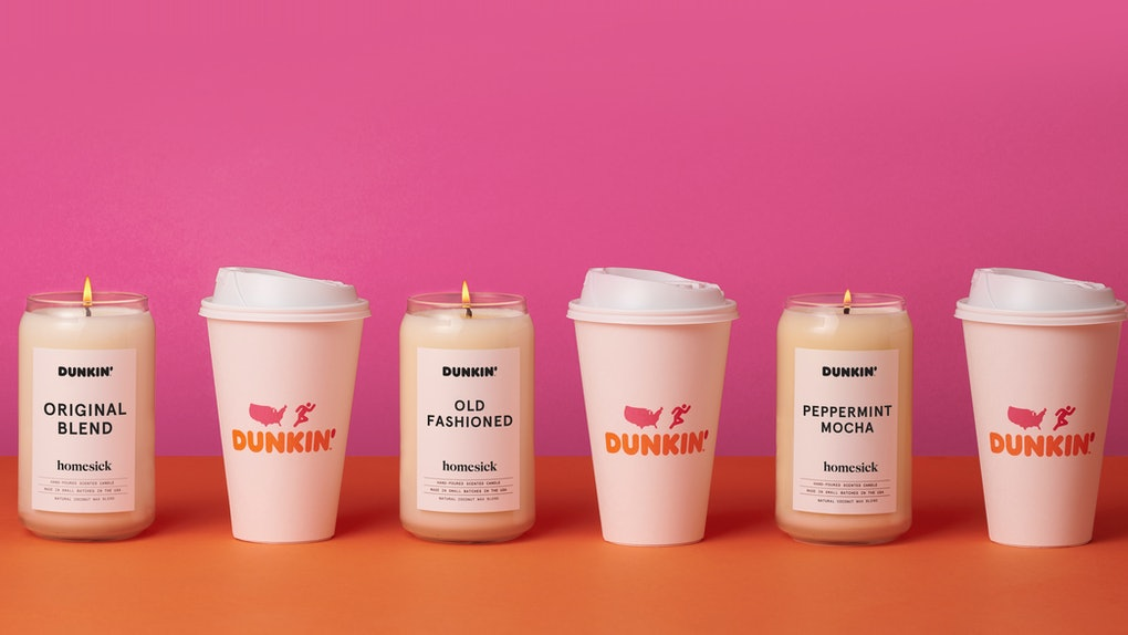 The Dunkin' x Homesick candles are lined up against a pink and orange background with Dunkin' coffee cups in between.