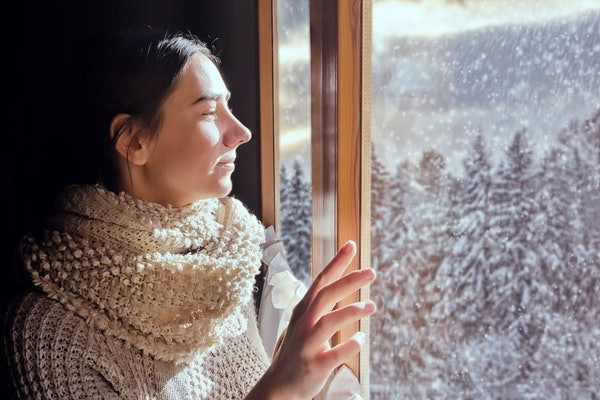 Young woman looking at snowy forest during December full moon