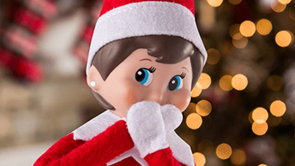 An Elf on the Shelf doll in front of a Christmas tree