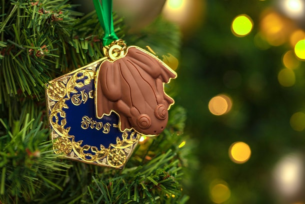 The chocolate frog ornament hangs on a Christmas tree.