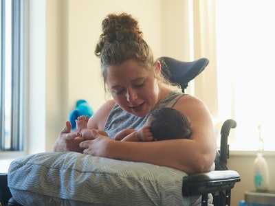 New mom holds baby in her chair