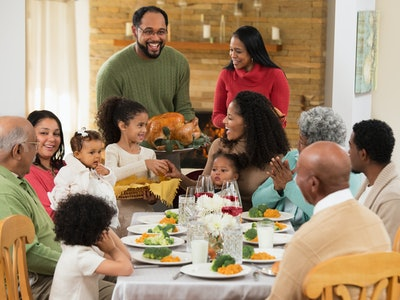 family sits around Thanksgiving table