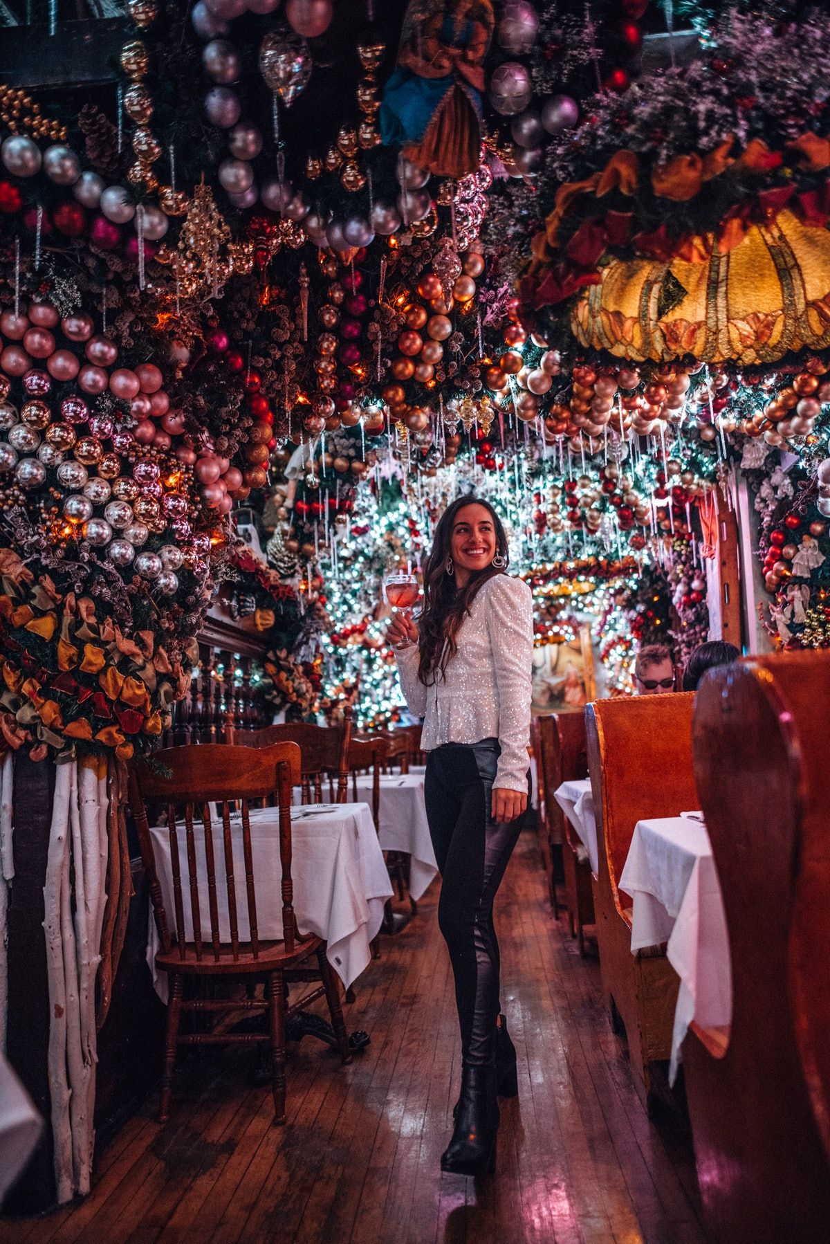 A travel blogger poses in Rolf's in New York City with a drink during the holidays.
