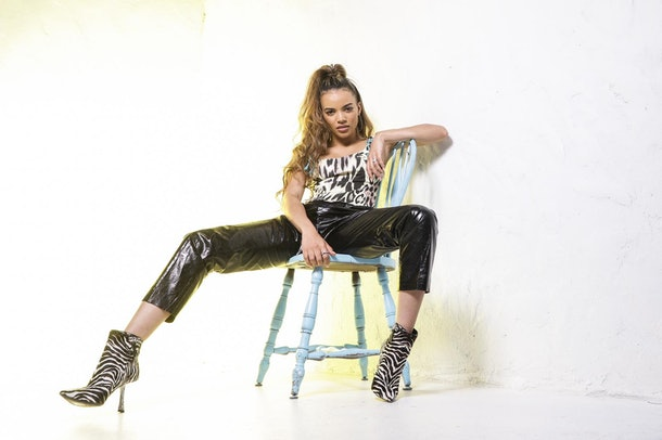 Leslie Grace poses against a white wall.