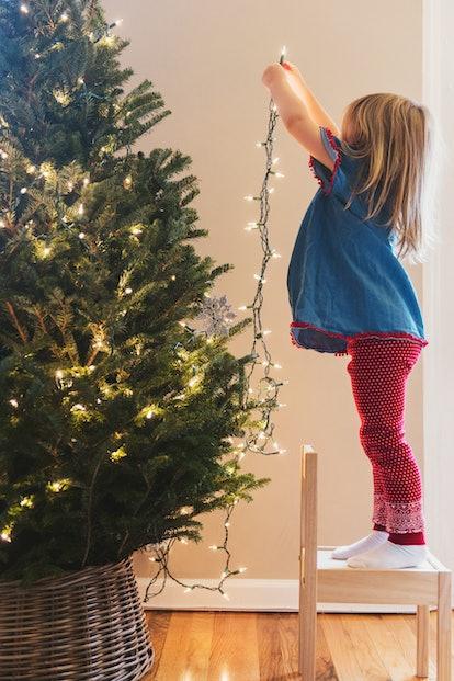 Little girl decorates Christmas tree