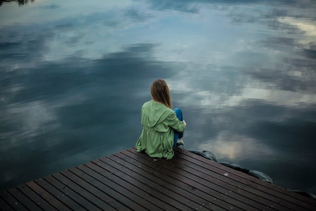 A woman sits on wooden planks. We can feel unable to cry for many reasons, including internalized shame, concern about vulnerability and cultural beliefs.