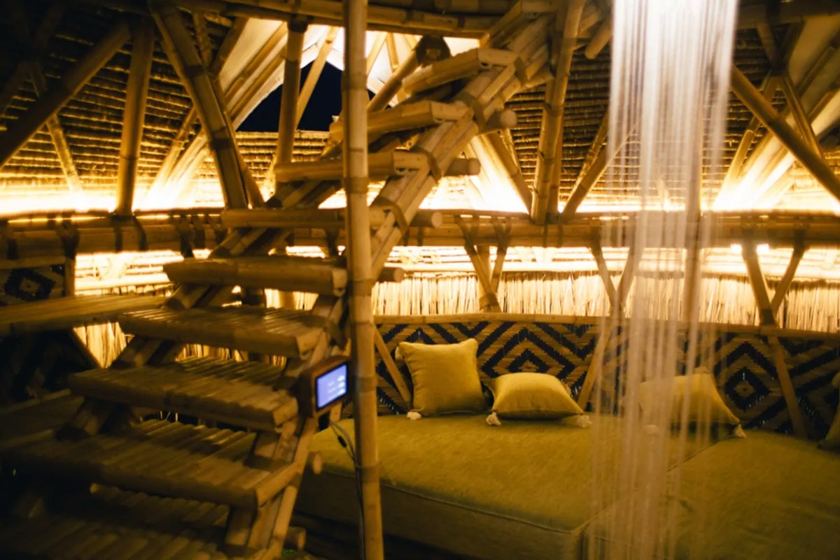 A dimly-liy room is surrounded by bamboo walls, with a bamboo staircase and a small couch.