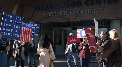 Regina King as Angela Abar walks into the Greenwood Center for Cultural Heritage while people protest Redfordations