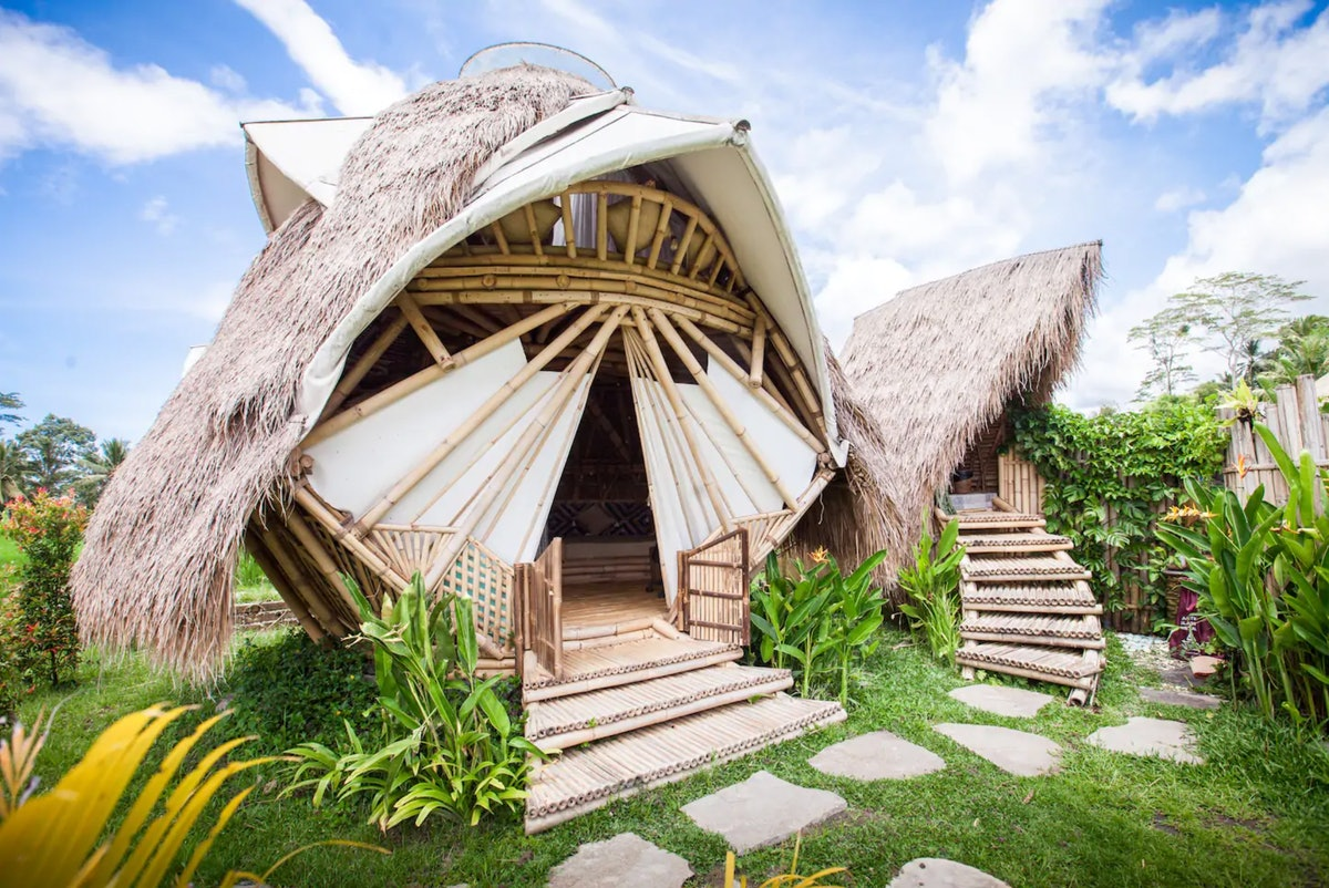 A geometric bamboo hut with steps that lead up to an entrance, and a smaller outhouse hut to the rig...