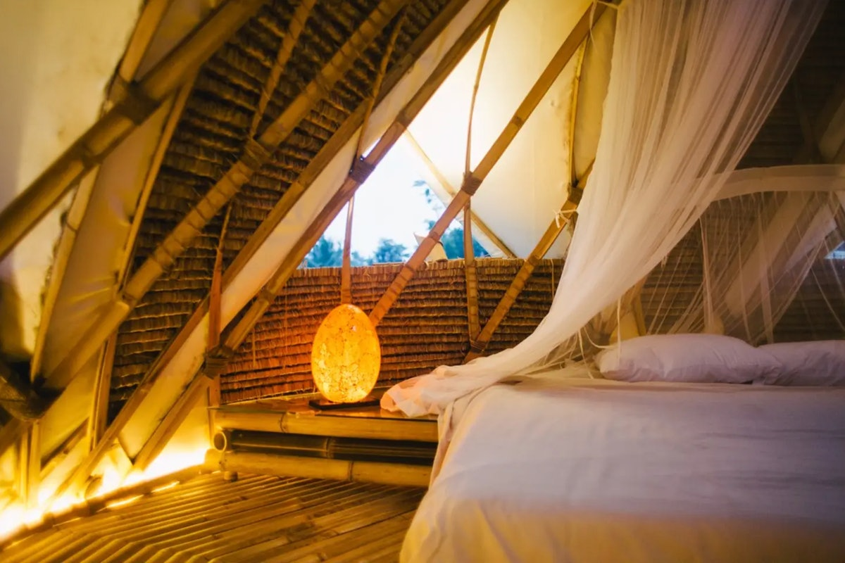 A dimly-lit bedroom shows part of a king bed covered by a mosquito net, a crystal lamp, and bamboo w...