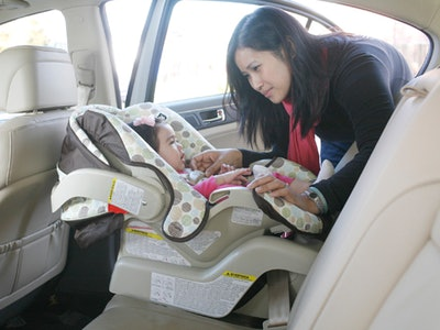 a mom buckling her baby into a car seat