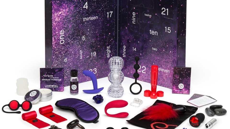 A midnight colored box style Advent calendar with an array of small sex toys placed before it.