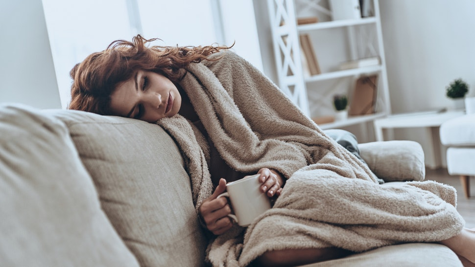 A person curls up on a couch with a blanket and a mug. Not getting enough sleep can make you more anxious, a new study says.
