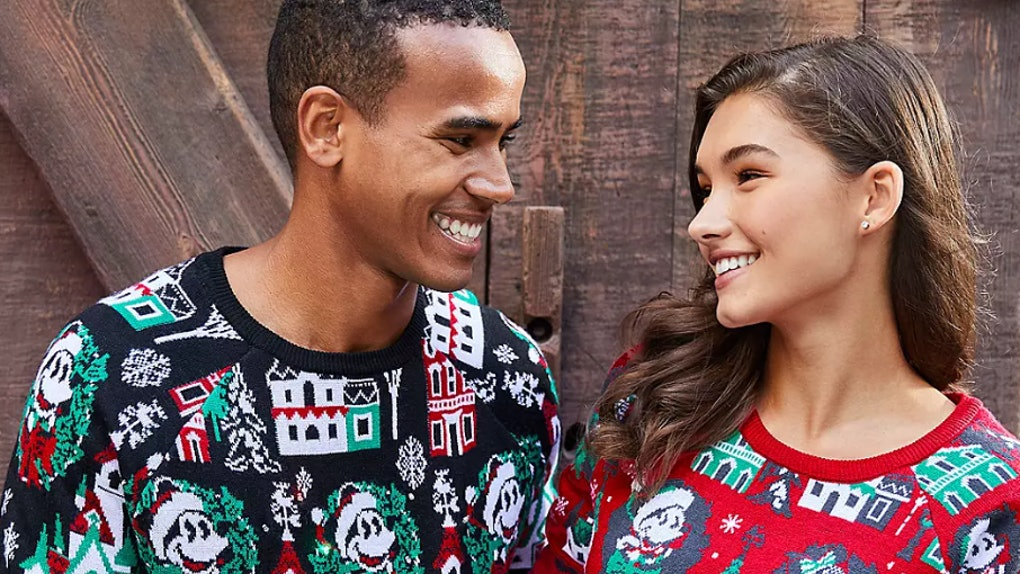 A man and woman wearing coordinating Disney holiday merchandise sweaters smile at each other.