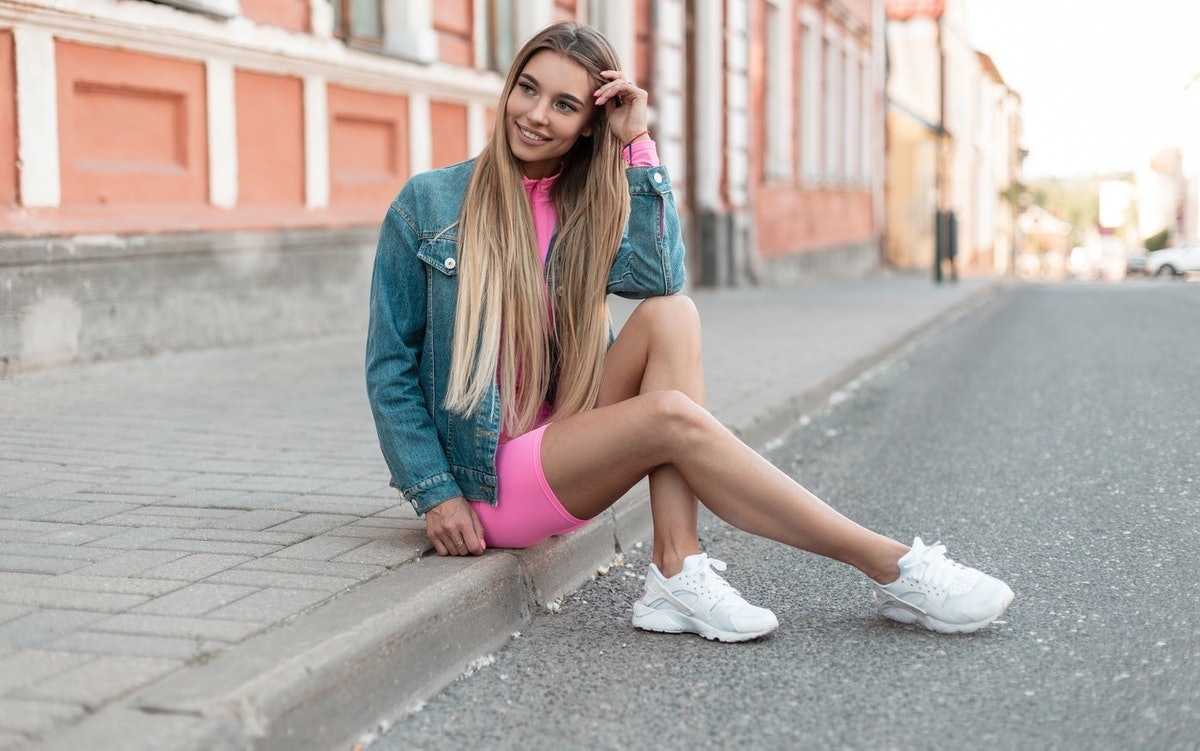 A blonde woman smiles and fixes her hair while she sits on the sidewalk in a denim jacket, pink mini dress, and white sneakers.