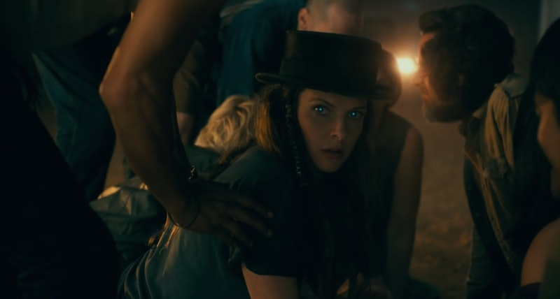 A brown-haired woman wearing an old black hat looks at the camera as an unnatural blue glow fills her eyes.