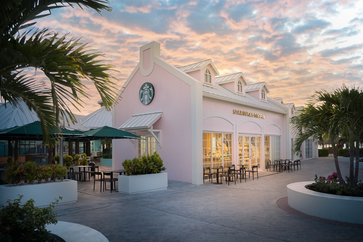 The exterior of Starbucks' Grand Turk store is millennial pink and surrounded by palm trees.