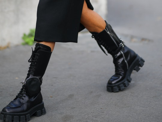 A close-up street style photo of a woman wearing black Prada combat boots at Paris Fashion Week Spring 2020.