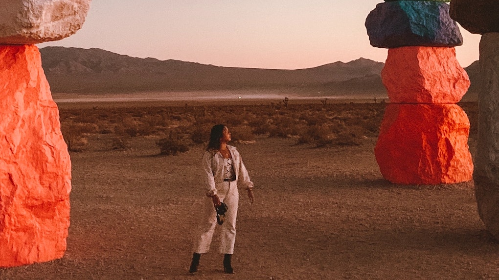 A woman stands in the desert surrounded by colorful rock installations looking off into the distance.