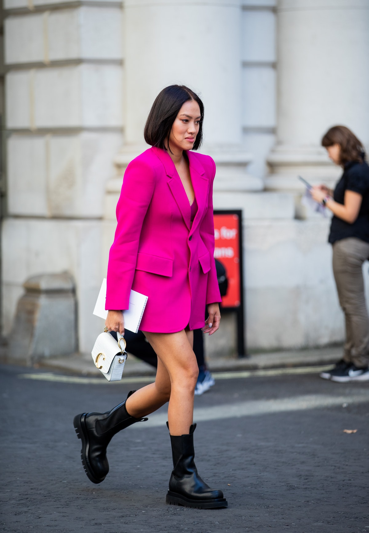 Street style photo of Tiffany Hsu wearing a pink blazer dress and combat boots at London Fashion Wee...