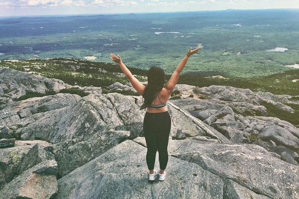 A girl with her back turned to the camera stands at the peak of a mountain looking out over a forest of green trees.