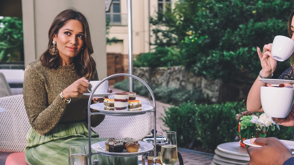 A stylish woman enjoys holiday afternoon tea and food with friends at Waldorf Astoria Atlanta Buckhead.
