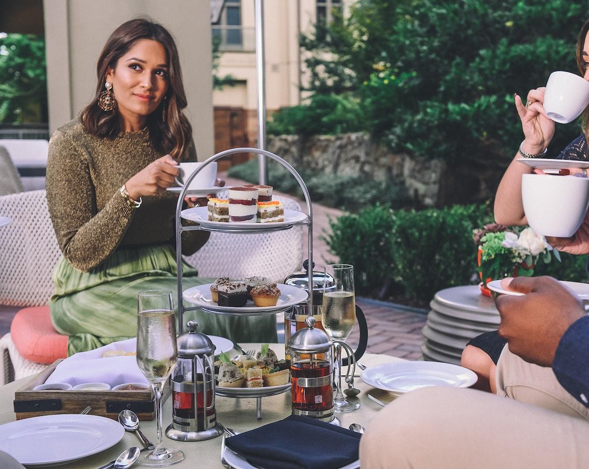 A stylish woman enjoys holiday afternoon tea and food with friends at Waldorf Astoria Atlanta Buckhe...